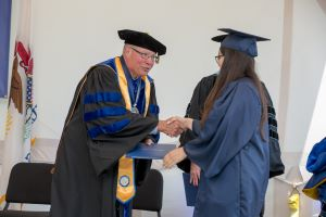 Dr. Ender shakes the hand of a Harper College graduate