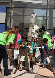 Students look through telescope at Harper College Expo