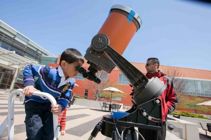 A young student looks through a telescope at Harper's College and Career Expo