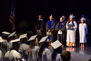 Harper's trustees, administrators and HSE graduation speakers stand on the stage