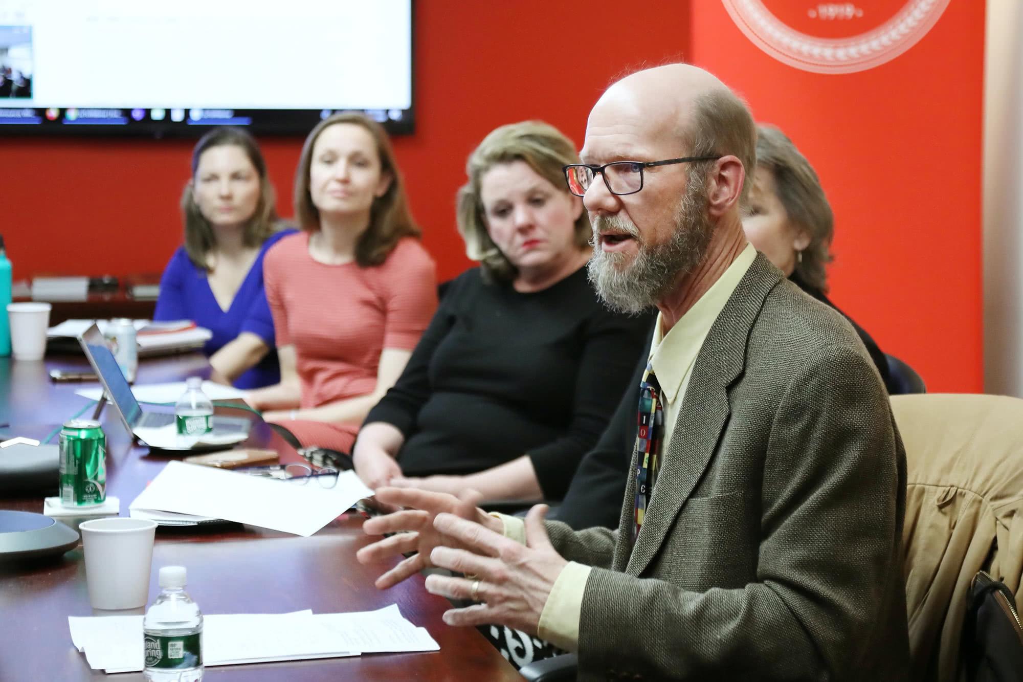 Richard Johnson en una mesa dirigiéndose a un grupo de personas
