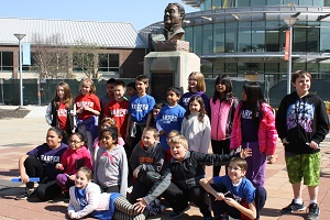 Ambassador School tour group takes picture in front of William Rainey Harper bust