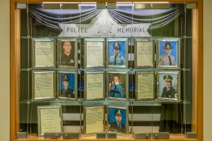 A display case features the photographs and bios of 7 fallen police officers
