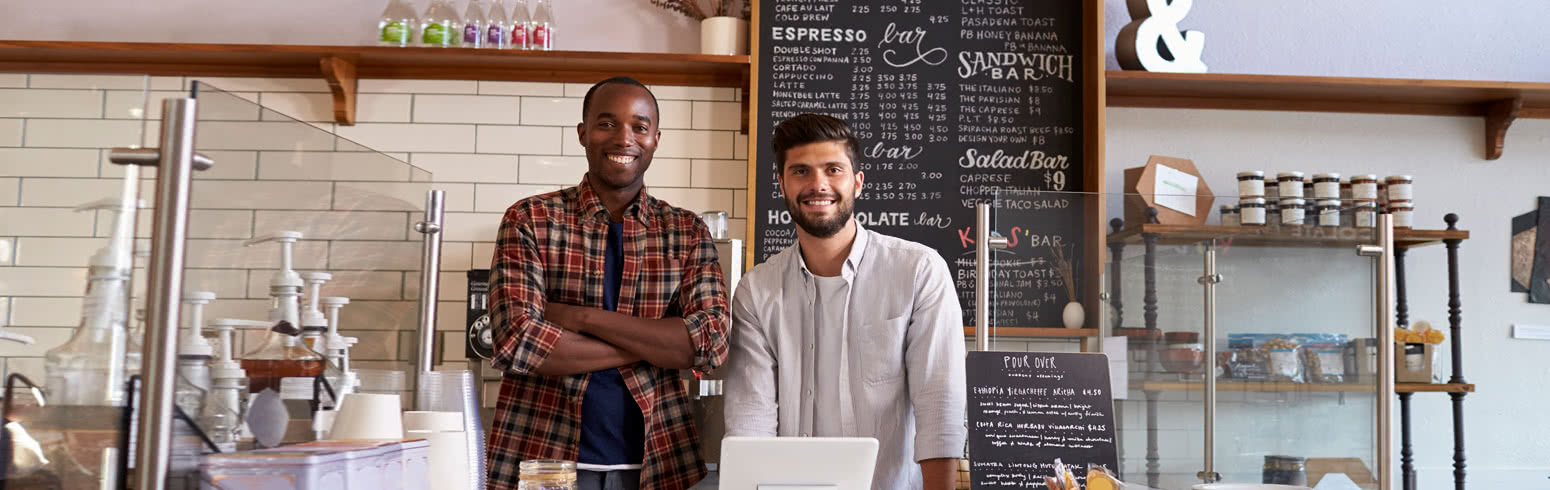 Two business partners standing in their cafe.