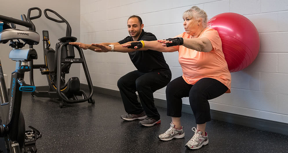 Physical therapist assistant helping old man with exercise and movement