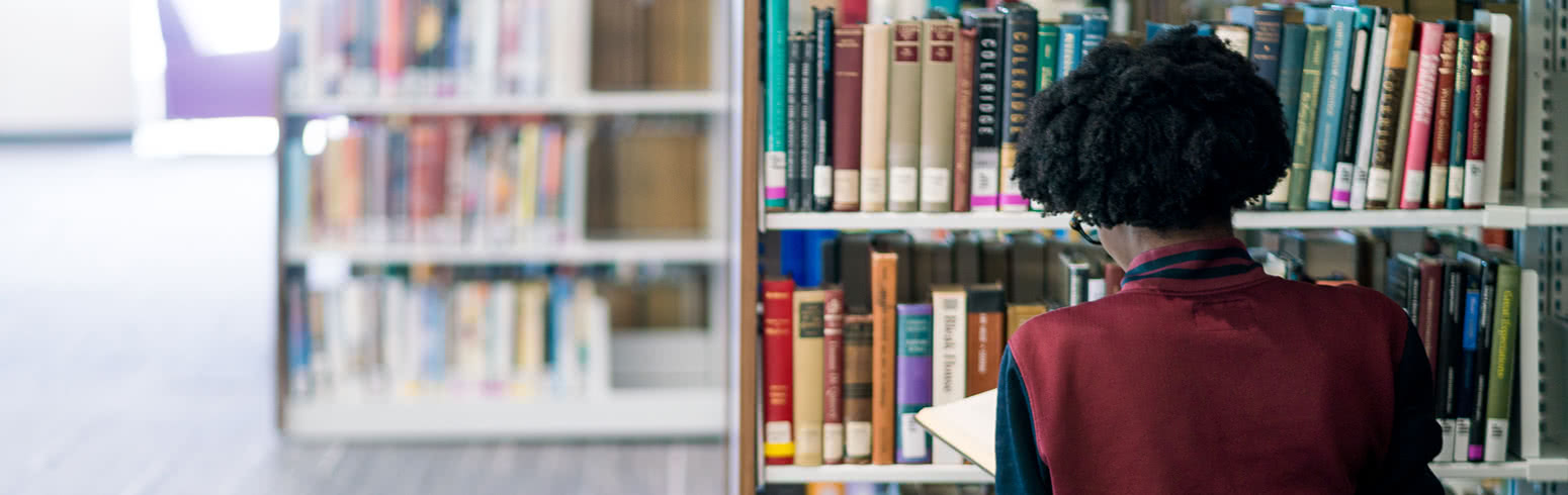 Student looking at books in library