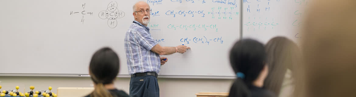 Professor explains chemistry formulas on whiteboard