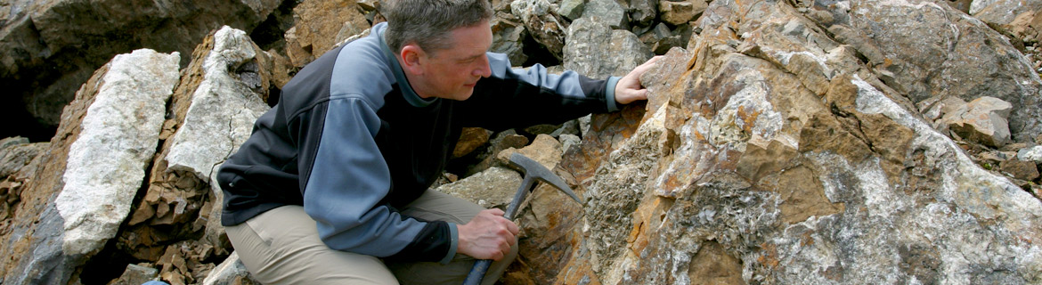 Man working with rocks and minerals in a geological setting