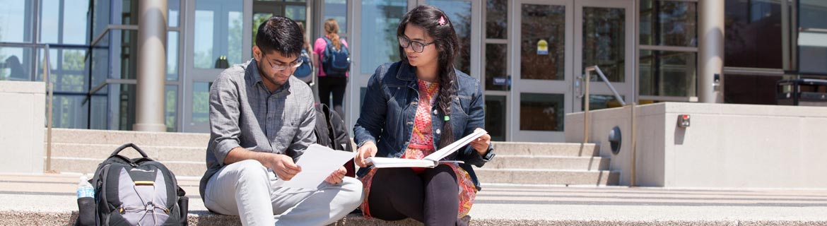 Two Harper students sit on steps outside Avante