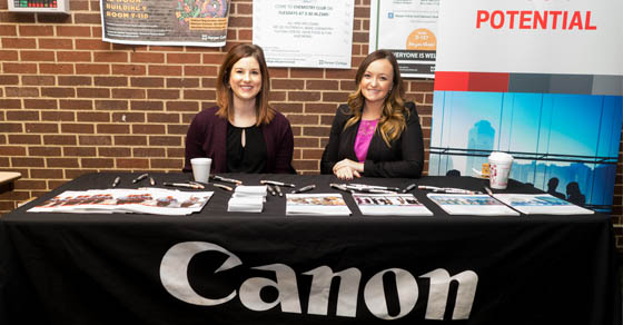 Two Canon representatives sitting at a booth at a past Graphic Arts Print Expo