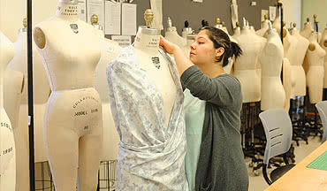 fashion designer pinning up a dress design