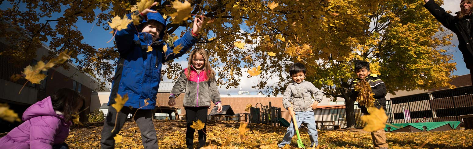 Children playing in leaves at the Early Childhood Laboratory School.