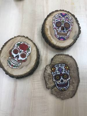 image of skull candy skeletons engraved on a piece of wood made with a vinyl cutter