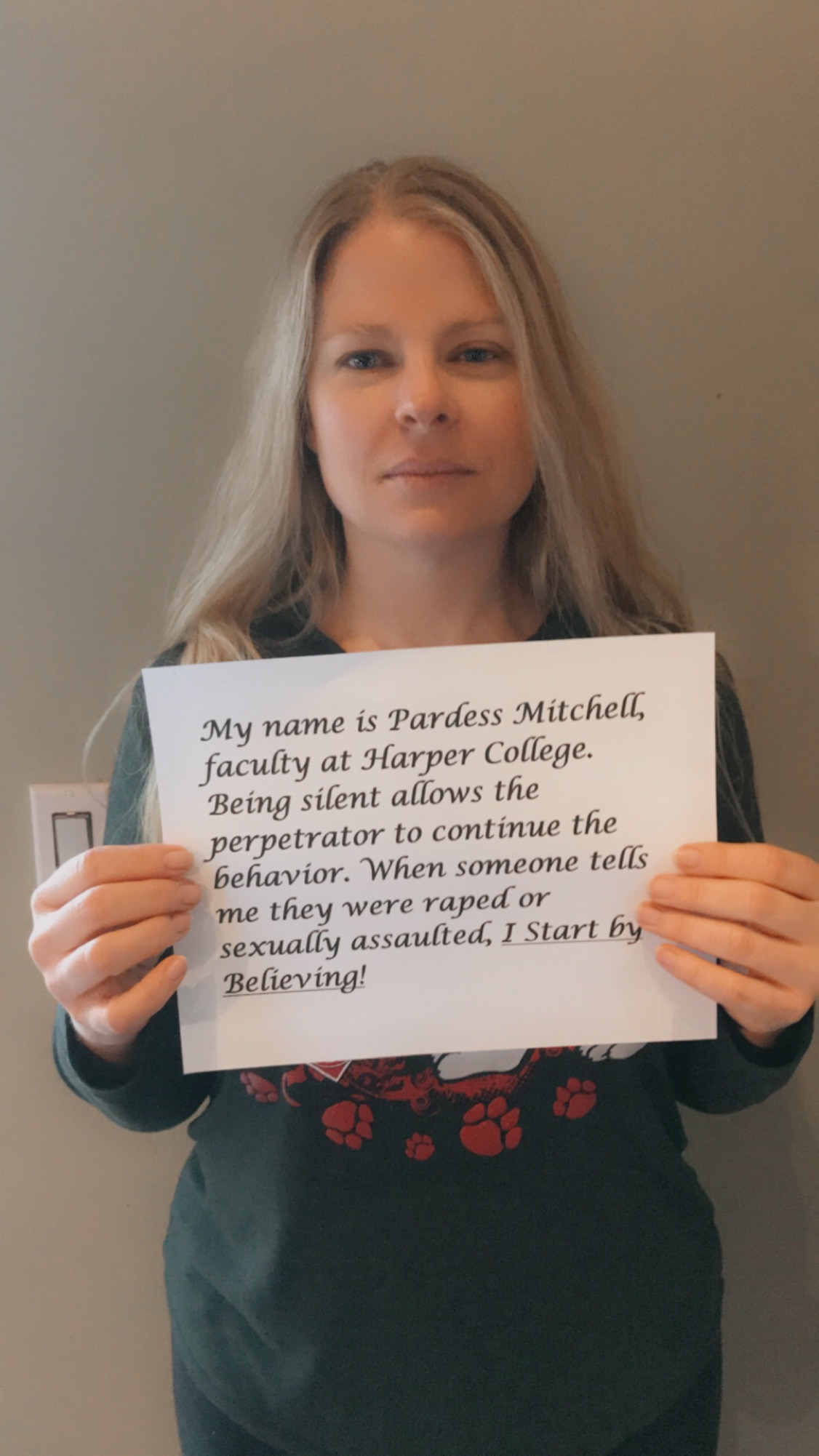 Photo of Pardess Mitchell holding up a sign with her name on it and the words,