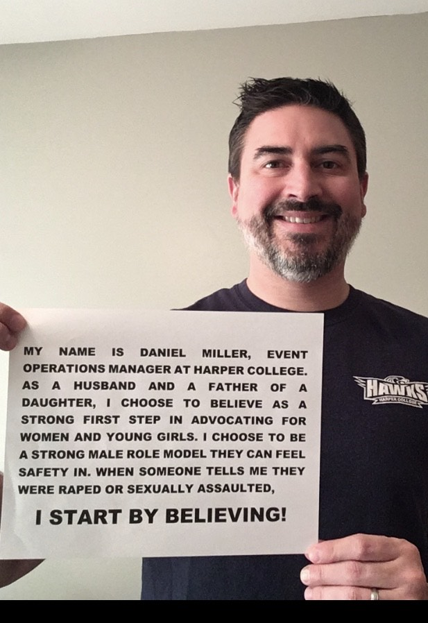 "Photo of Daniel Miller holding up a sign with his name on it with the words, ""I start by believing."""